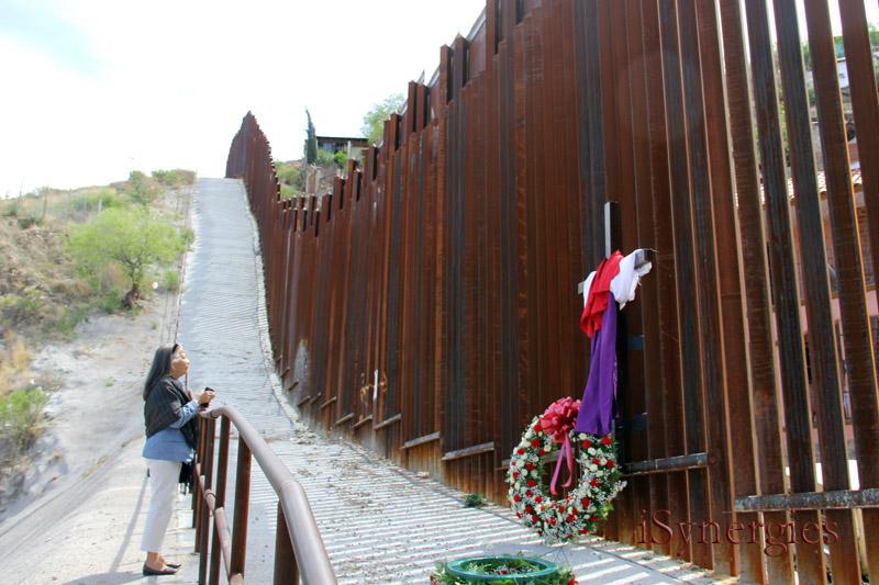Decir una oración a lo largo del muro de la frontera en Nogales